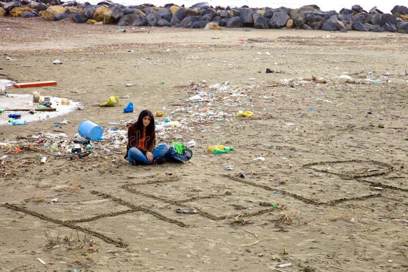 Femme désespérée au sujet de la saleté et de la pollution sur la plage demandant l'aide photos libres de droits