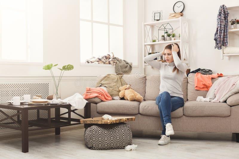 Femme désespérée s'asseyant sur le sofa dans la chambre malpropre photos stock