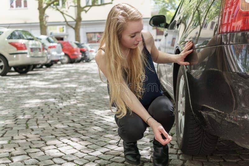 Femme désespérée vérifiant les dommages à sa voiture image libre de droits