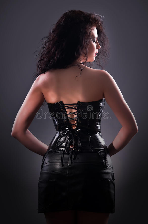 Femme désirée de brunette posant dans le corset en cuir image libre de droits