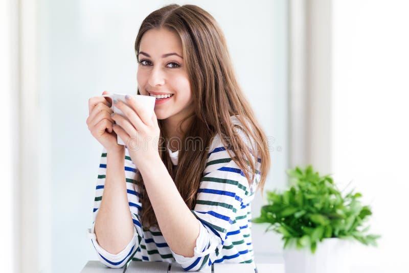 Femme détendant avec la cuvette de café photo stock