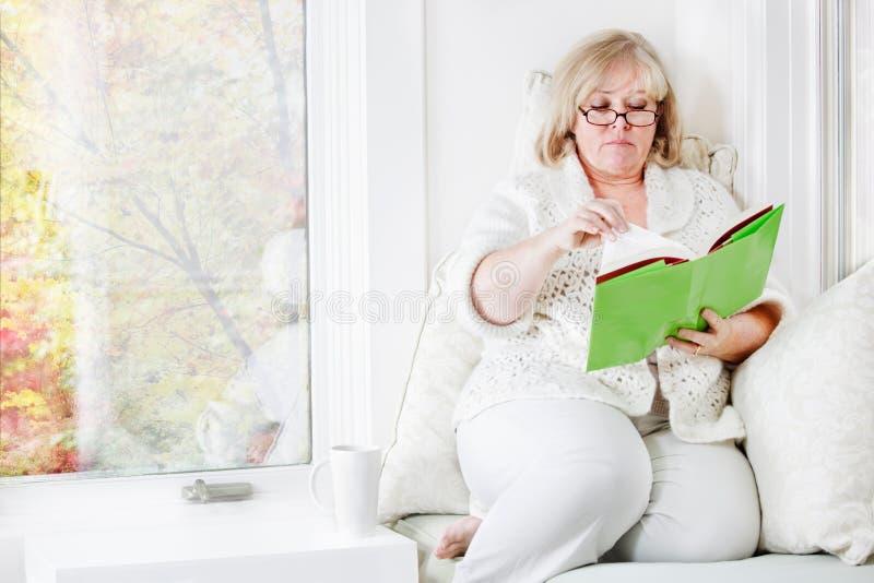 Femme détendant avec un livre photos libres de droits