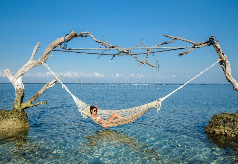 Femme détendant dans l'oscillation en mer de turquoise de paradis, images stock