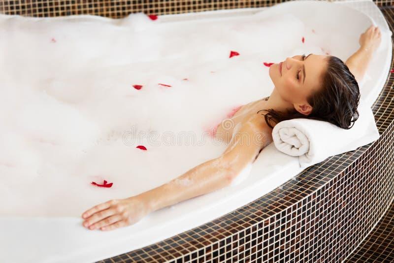 Femme détendant dans le bain moussant avec Rose Petals Soin de fuselage photo libre de droits