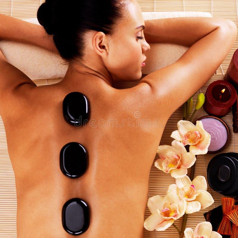 Femme détendant dans le salon de station thermale avec les pierres chaudes sur le corps photos libres de droits