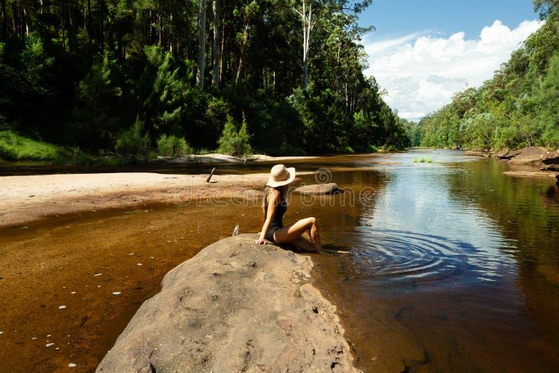 Femme détendant le long du bas-fond de la rivière de Grose photo stock