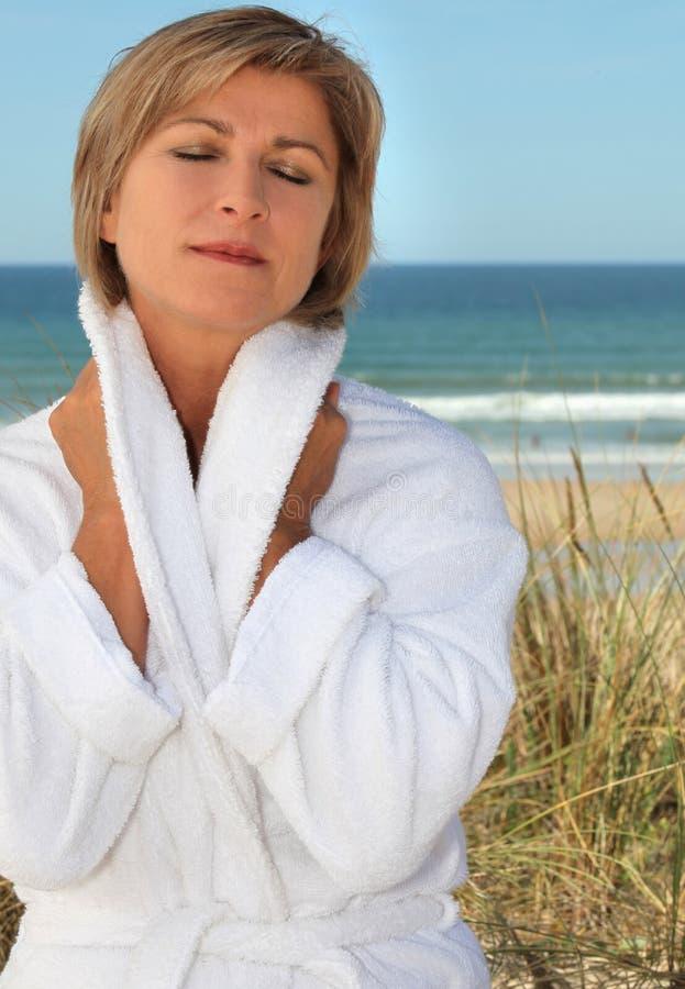 Femme détendant par le bord de la mer photographie stock
