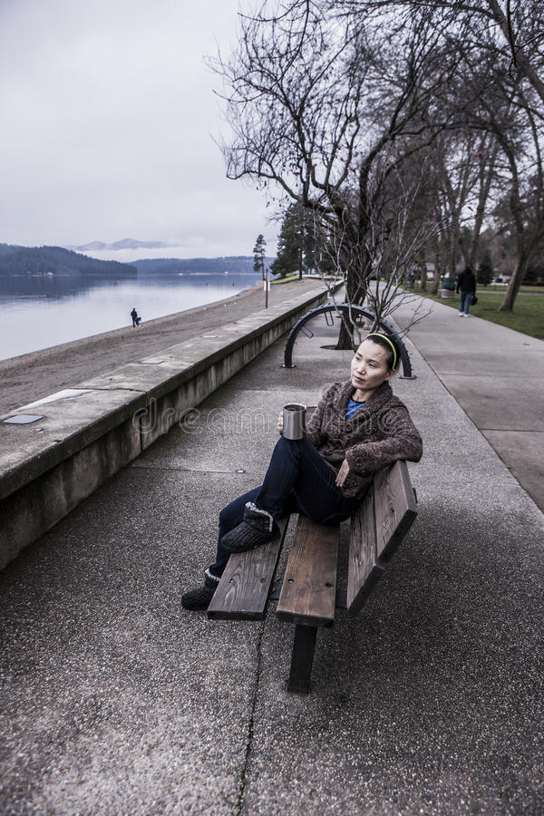 Femme détendant sur le banc de parc photos stock
