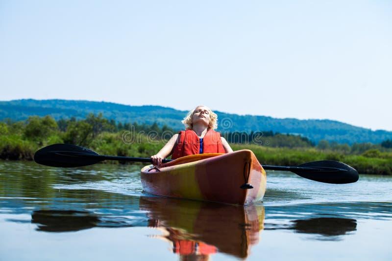 Femme détendant sur un kayak et appréciant sa vie image libre de droits