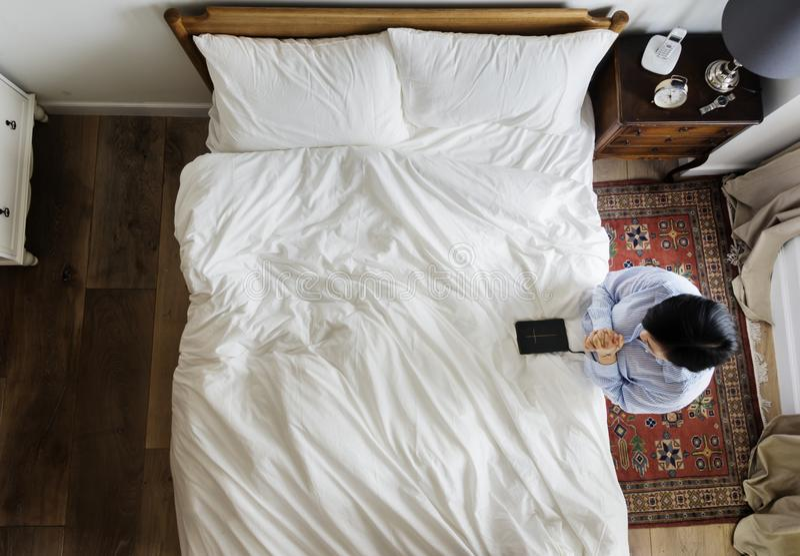 Femme dévotte avec un livre de bible priant par le lit image stock