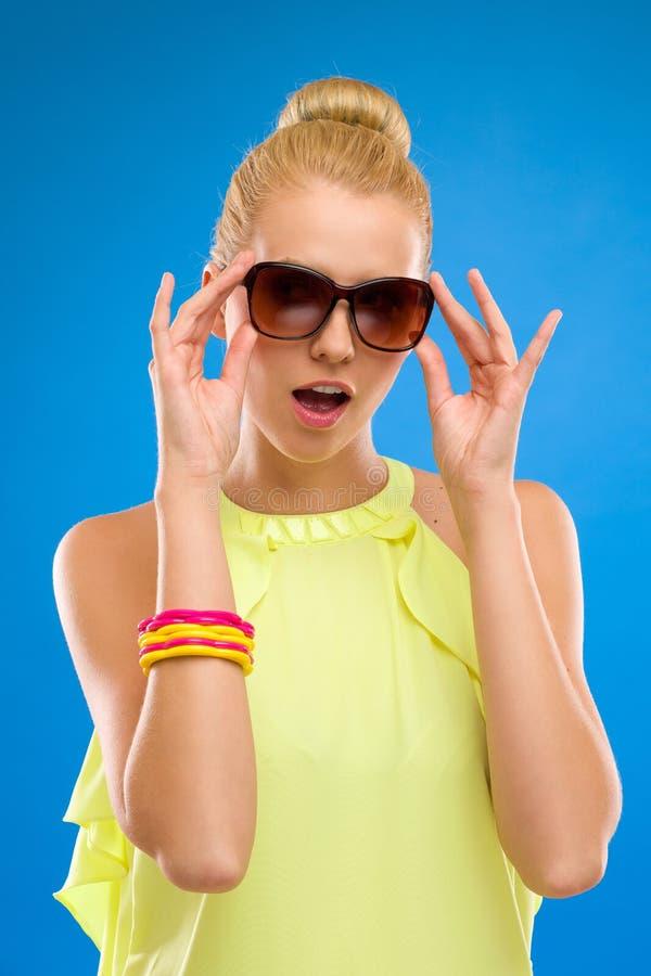 Femme d'élégance dans des lunettes de soleil sur le fond bleu. photos libres de droits