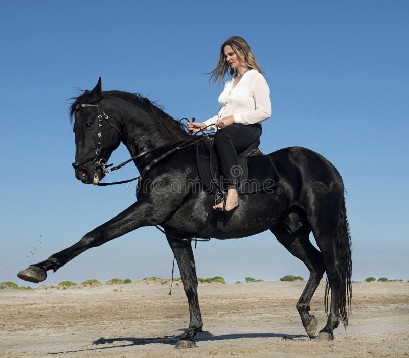 Femme d'équitation sur la plage image stock