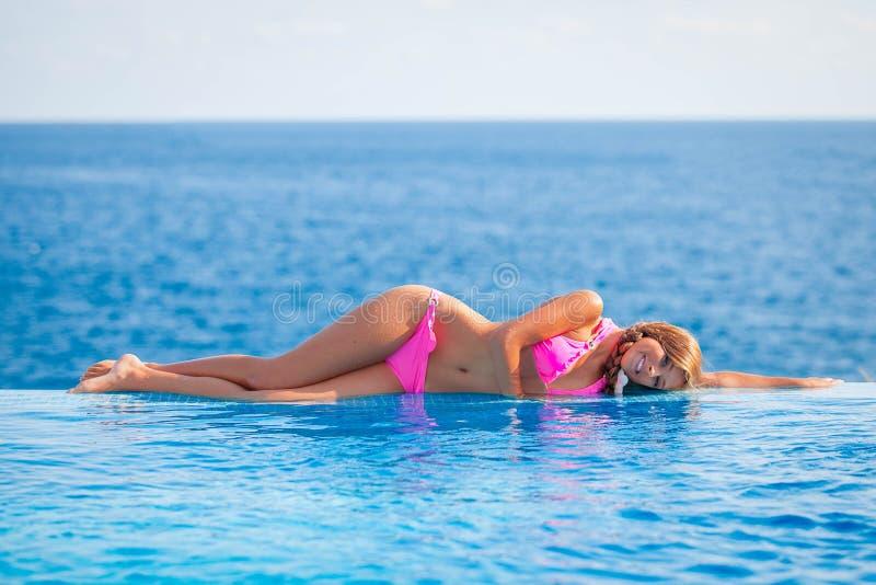 Femme d'été prenant un bain de soleil dans la piscine d'infini image libre de droits