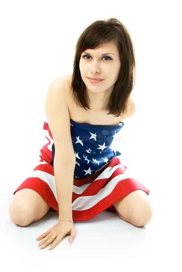 Femme enveloppée dans le drapeau américain sur le plancher