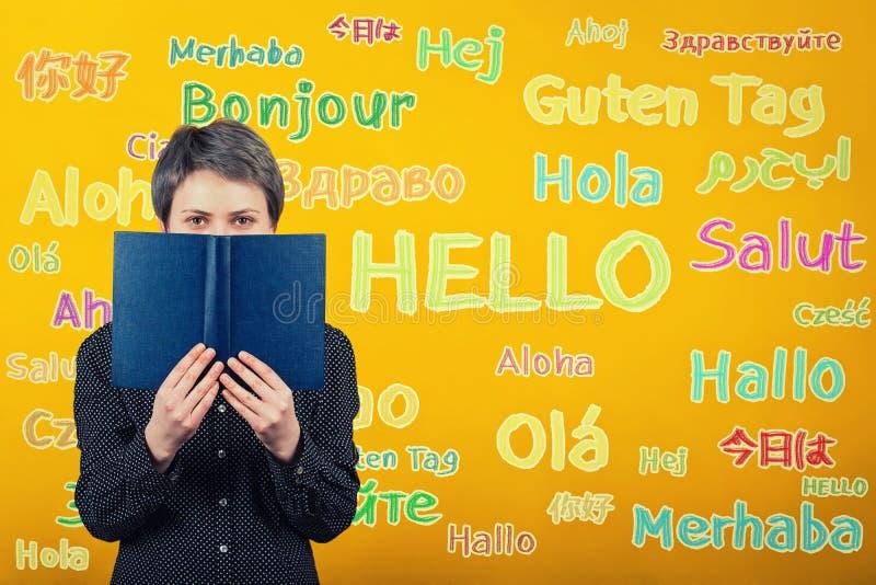 Femme d'étudiant tenant un manuel au-dessus du mur jaune écrit avec le mot bonjour traduit en différentes langues Occasion pour images libres de droits