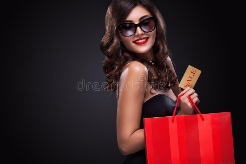 Femme d'achats jugeant le sac gris d'isolement sur le fond foncé dans des vacances noires de vendredi photographie stock