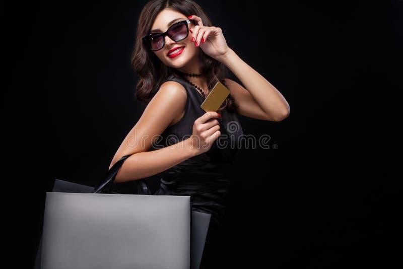 Femme d'achats jugeant le sac gris d'isolement sur le fond foncé dans des vacances noires de vendredi photo stock