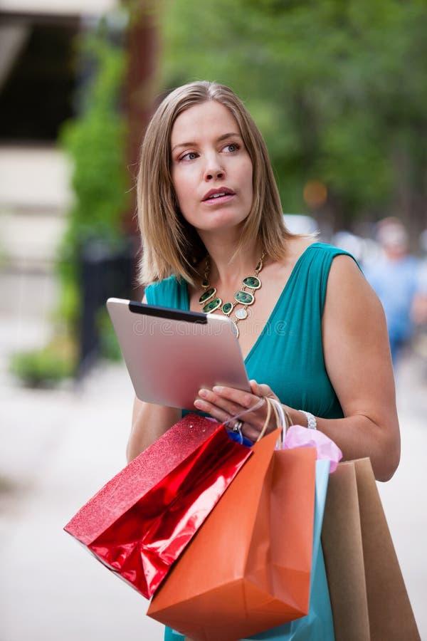 Femme d'achats tenant la Tablette de Digital photographie stock