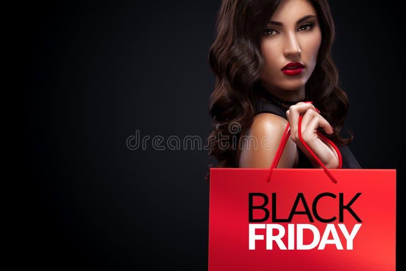 Femme d'achats tenant le sac rouge dans des vacances noires de vendredi image libre de droits