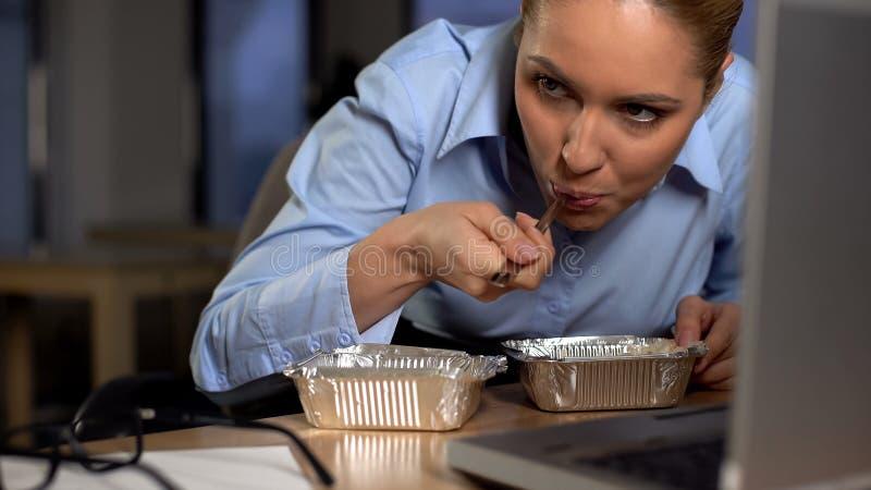 Femme d'affaire louche mangeant de la nourriture volée, se cachant sous l'ordinateur, manque d'argent image stock