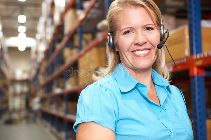 Femme d'affaires à l'aide de l'écouteur dans l'entrepôt de distribution photo stock