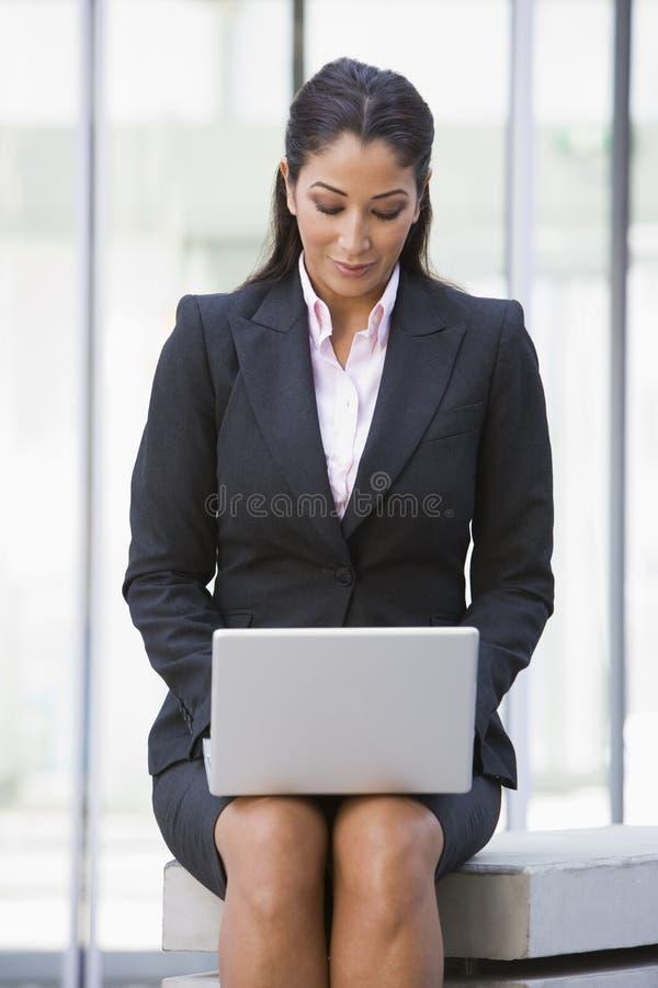 Femme d'affaires à l'aide de l'ordinateur portable à l'extérieur photo libre de droits