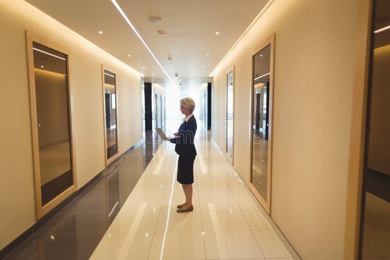 Femme d'affaires à l'aide de l'ordinateur portable dans le couloir image libre de droits