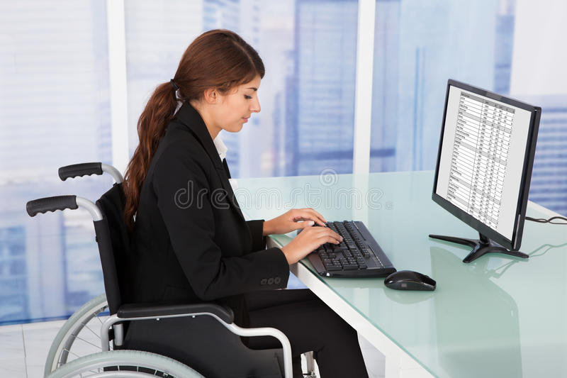 Femme d'affaires à l'aide de l'ordinateur tout en se reposant sur le fauteuil roulant photos libres de droits