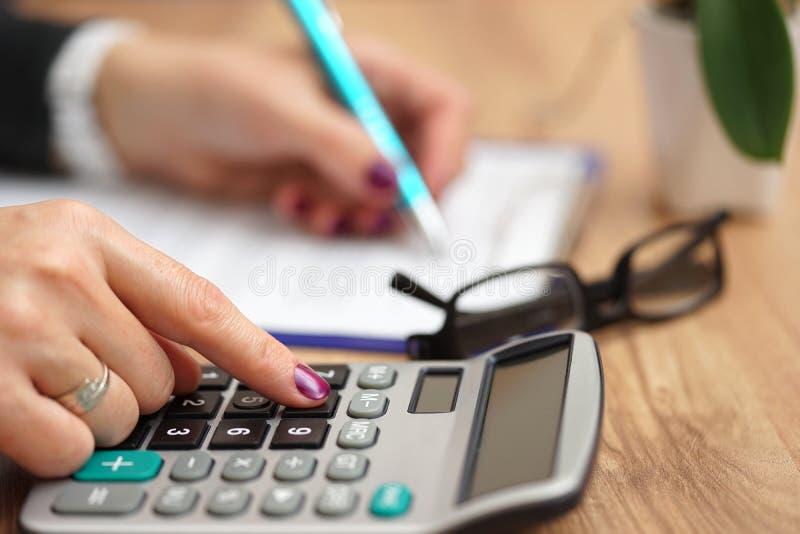 Femme d'affaires à l'aide de la calculatrice pour le document accomplissant pour elle photographie stock