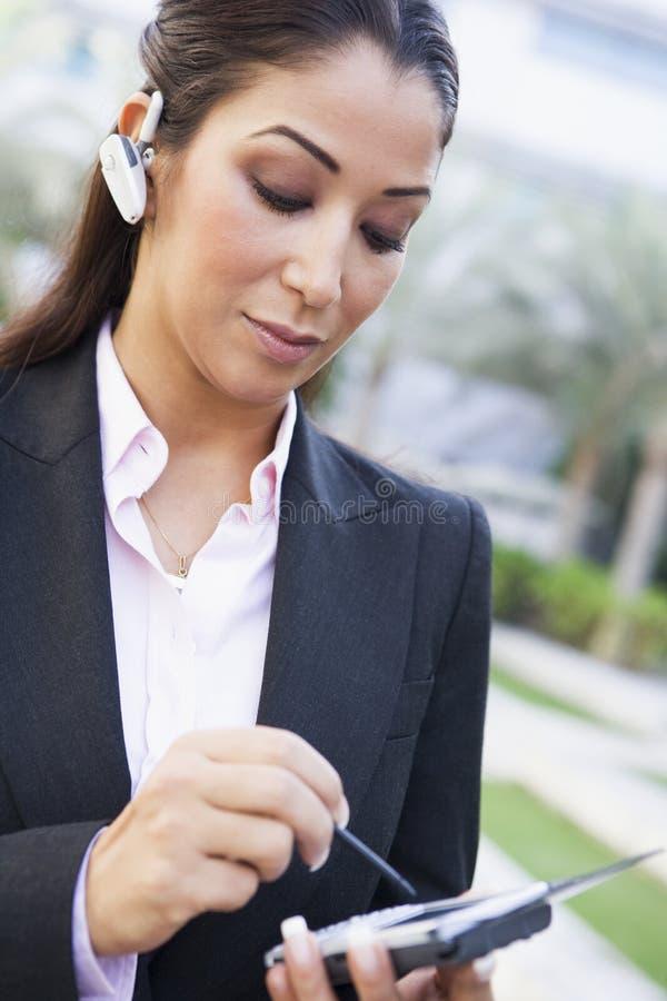 Femme d'affaires à l'aide de PDA et d'écouteur images stock