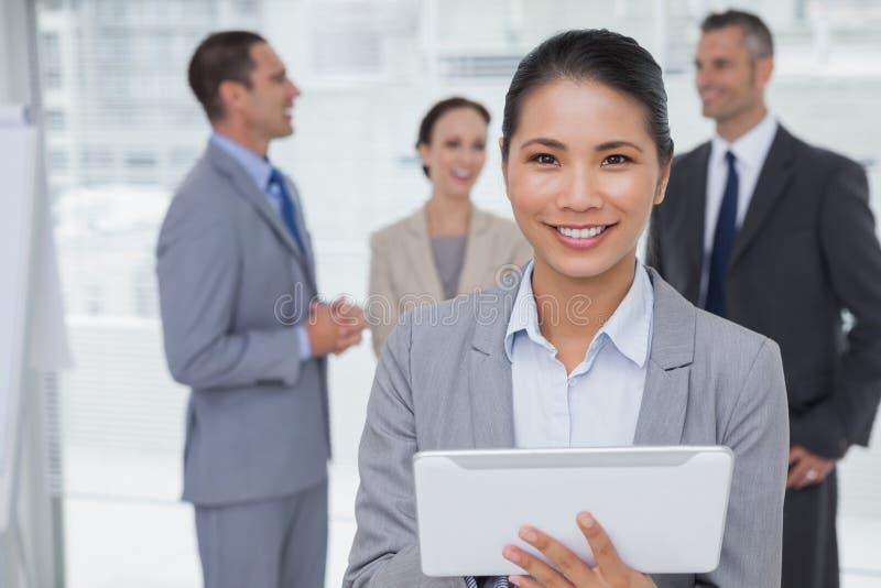 Femme d'affaires à l'aide de son PC de comprimé tandis que collègues parlant le toget photos stock