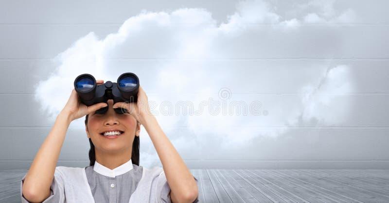 Femme d'affaires à l'aide des jumelles contre le ciel nuageux photos stock