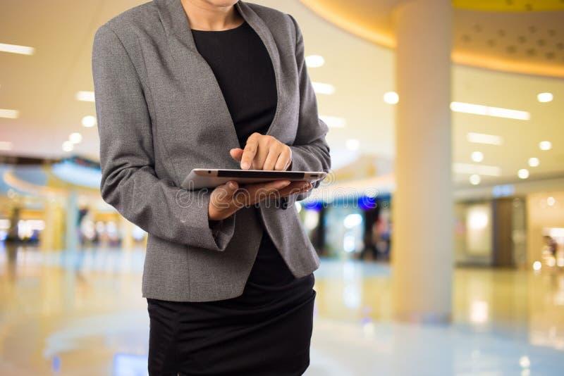 Femme d'affaires à l'aide du comprimé numérique dans le centre commercial images libres de droits