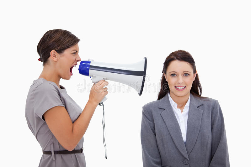 Femme d'affaires à l'aide du mégaphone pour hurler au collègue image stock