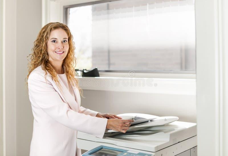 Femme d'affaires à l'aide du photocopieur dans le bureau photos stock