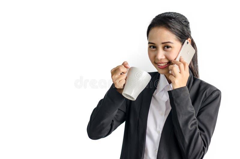 Femme d'affaires à l'aide du téléphone portable tout en tenant la tasse de café jetable photo stock