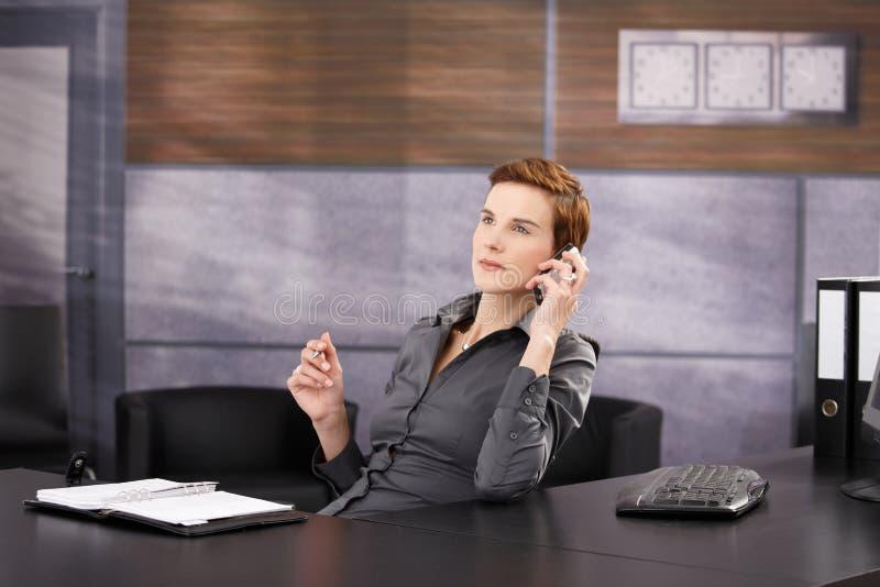 Femme d'affaires à l'appel de travail image stock
