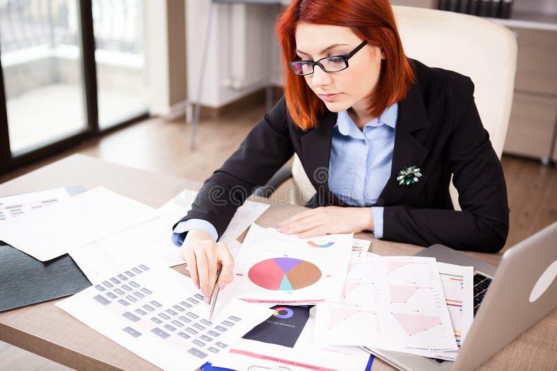 Femme d'affaires à sa table regardant des diagrammes images libres de droits