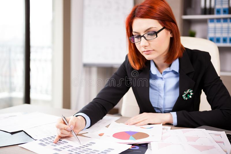 Femme d'affaires à sa table regardant des diagrammes photo stock