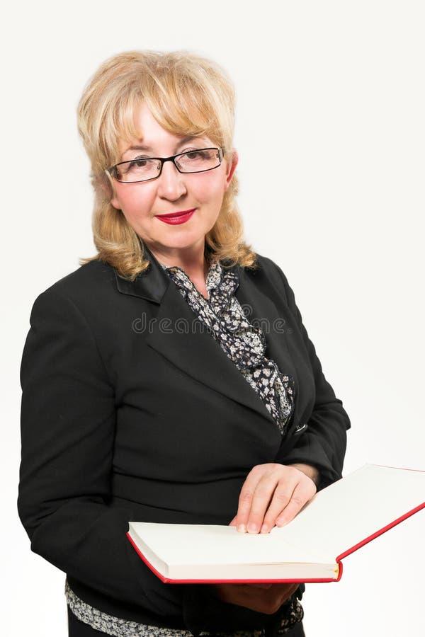 Femme d'affaires âgée par milieu, tenant le carnet photographie stock