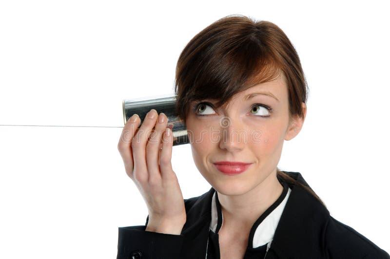 Femme d'affaires écoutant le téléphone de boîte en fer blanc photographie stock