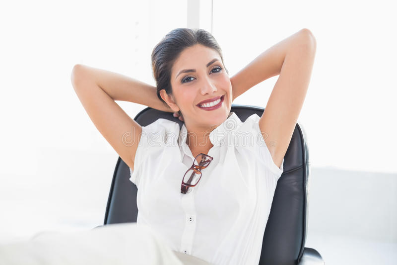Femme d affaires étendue s asseyant à son bureau souriant à l appareil-photo