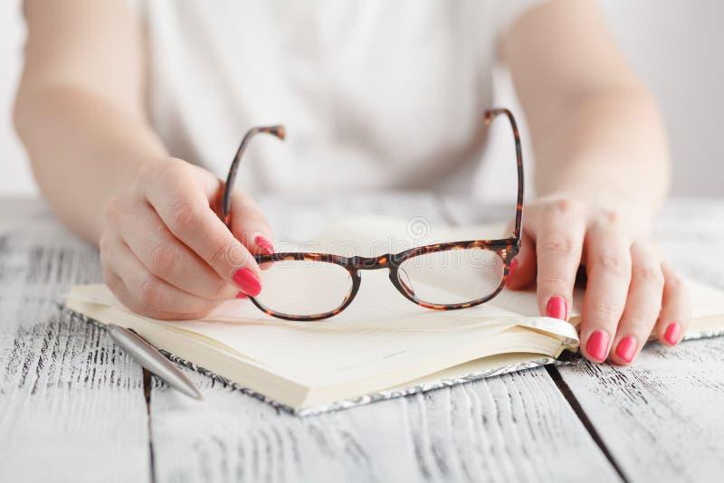 Femme d'affaires étonnée enlevant des verres tout en lisant dans le bureau images stock