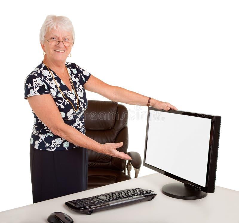 Femme d'affaires aînée dirigeant un moniteur photo stock