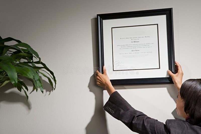 Femme d'affaires accrochant le certificat encadré photo libre de droits