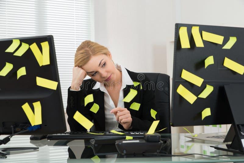 Femme d'affaires With Adhesive Notes dans le bureau images libres de droits