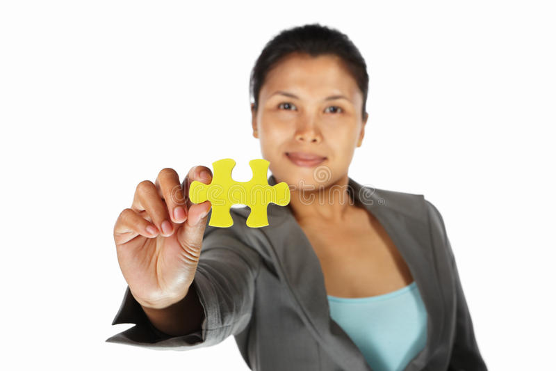 Femme d'affaires affichant la partie de puzzle de jigzaw image libre de droits