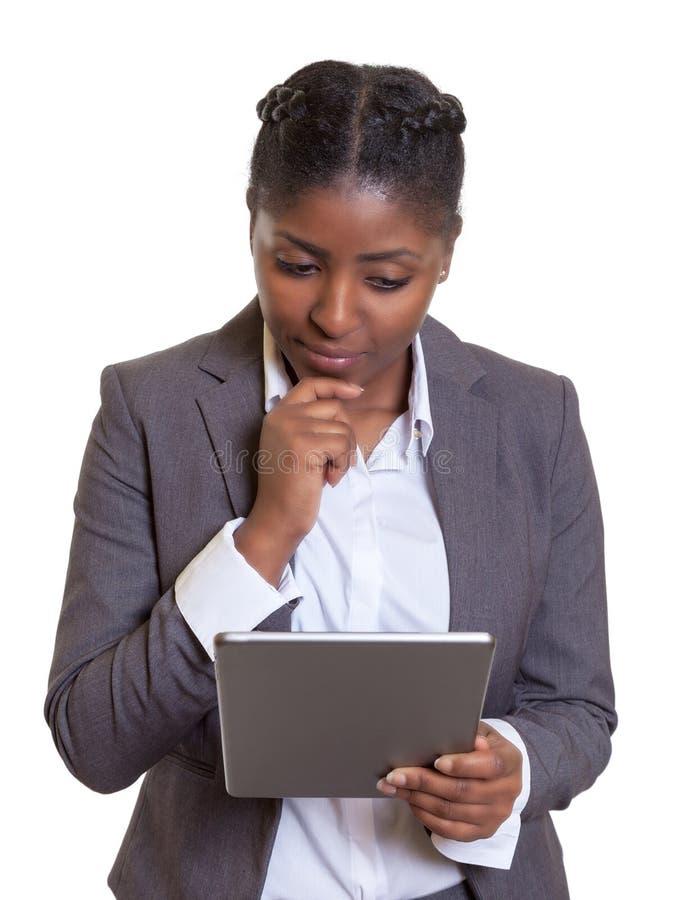 Femme d'affaires africaine de pensée avec la tablette moderne photos libres de droits