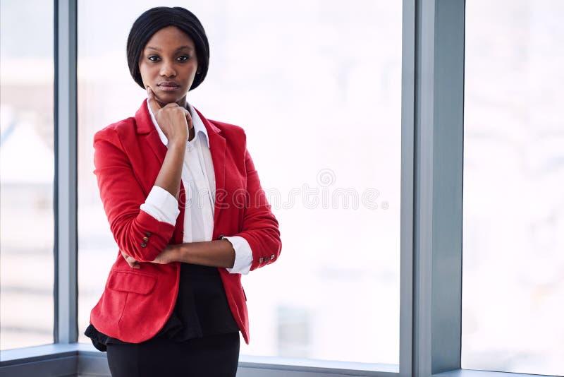 Femme d'affaires africaine regardant dans l'appareil-photo avec confiance tout en utilisant le blazer rouge images stock