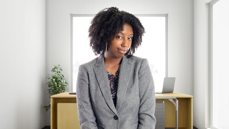 Femme d'affaires In d'afro-américain un bureau semblant timide ou embarrassé image libre de droits